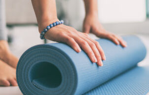 oga at home active lifestyle woman rolling exercise mat in living room for morning meditation yoga banner background.
